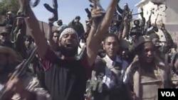 Gambar dari televisi ini menunjukkan para tentara di Libya merayakan direbutnya kota Sirte, Kamis (20/10).
