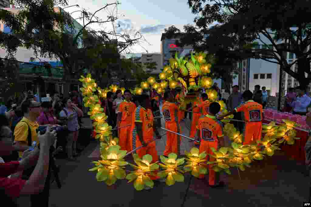 Local performers display dragon laterns during a media preview of the upcoming mid-autumn festival in Singapore.