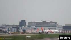 FILE - Aircraft taxi at Gatwick Airport in southern Britain, Dec. 17, 2015. British officials say three men and a woman were taken into custody in Birmingham Thursday, while another man was held at London's Gatwick Airport on Friday, April 15, 2015.