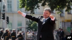 Presiden Ukraina Petro Poroshenko mengangkat tangannya menyambut hadirin seusai pelantikannya sebagai Presiden di Lapangan Sophia, Kyiv, Ukraina (7/6).