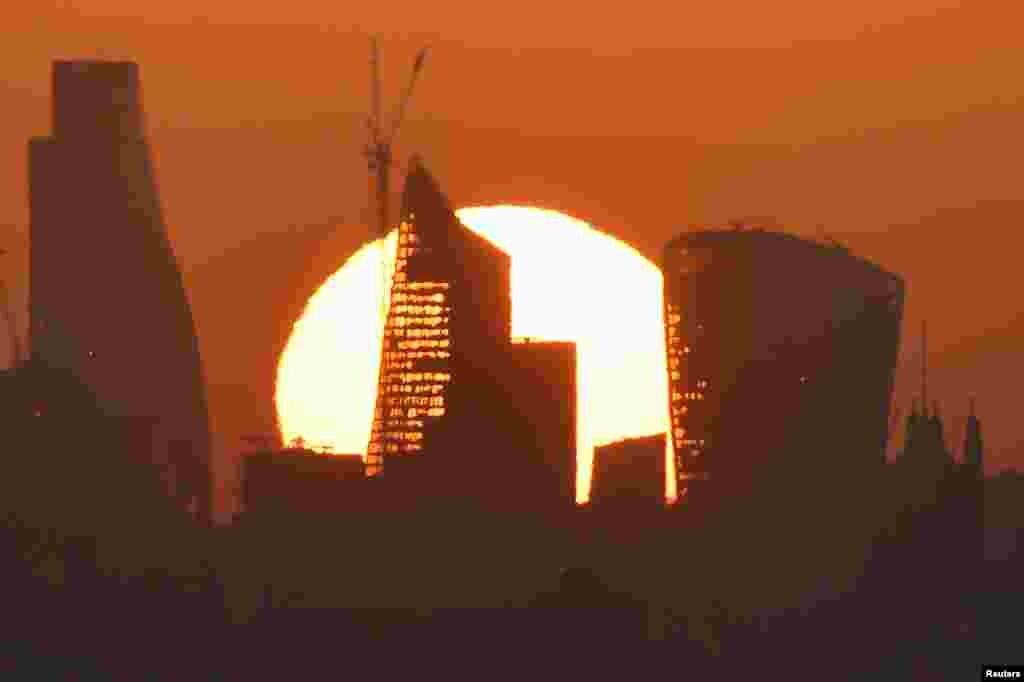 The sun is seen rising over skyscrapers in London's financial district.
