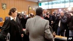 Onesphore Rwabukombe est photographié par les médias alors qu'il attend le début de son procès devant un tribunal de Francfort, centre de l'Allemagne, mardi 18 janvier 2011.