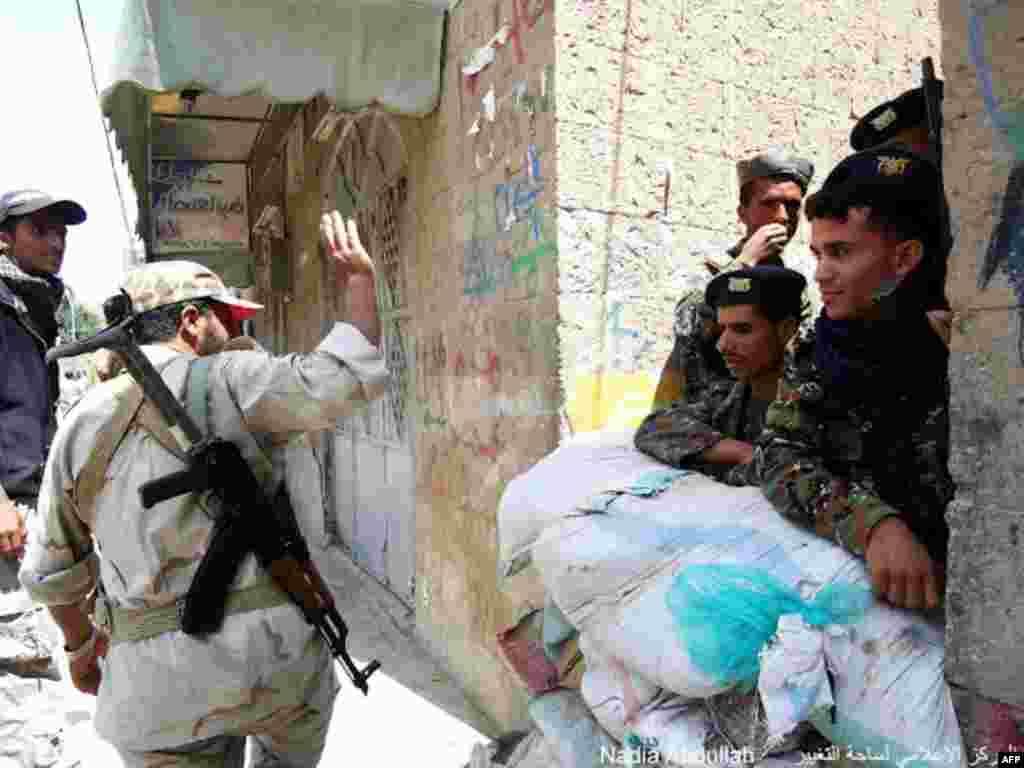 Một người lính vẫy chào những thành viên lực lượng an ninh (Ảnh: Nadia Abdullah)