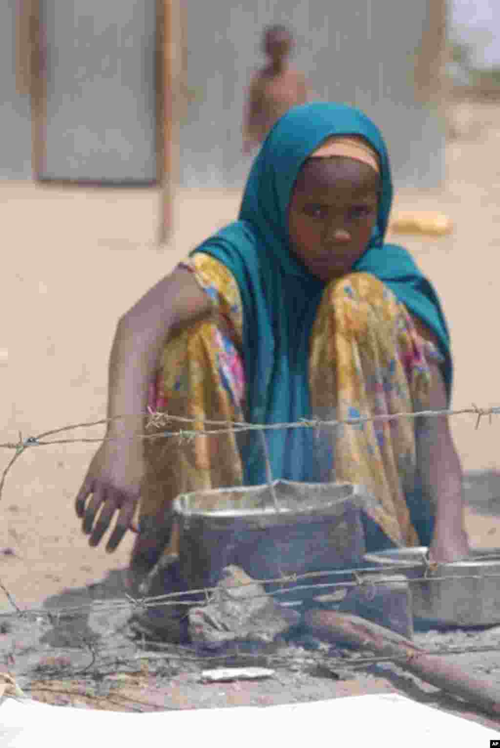 A girl warms some food on a makeshift fire shortly after arrival at the Dollo Ado refugee reception center. VOA - P. Heinlein