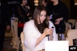 2013年12月郭美美在北京的首饰拍卖会上看手机。这位美女搅动了中国网络和慈善捐款方面的一池春水