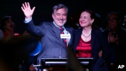 Alejandro Guillier, left, of the Nueva Mayoria coalition celebrates with his wife, Maria Cristina Farga, early results that place him second in the presidential election, in Santiago, Chile, Nov. 19, 2017.