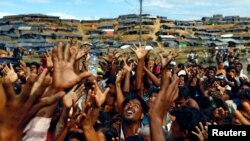 Rohingya refugees stretch their hands to receive aid distributed by local organisations at Balukhali makeshift refugee camp in Cox's Bazar, Bangladesh, September 14, 2017.