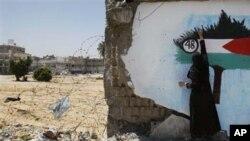 파괴된 벽에 팔레스타인 기를 그리고 있는 가자지구의 여인