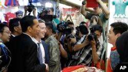 Pendiri Facebook Mark Zuckerberg (dua dari kiri) bersama Presiden Terpilih Joko Widodo (kiri) berbincang dengan salah seorang pedagang saat 'blusukan' di pasar Tanah Abang, Jakarta (13/10).