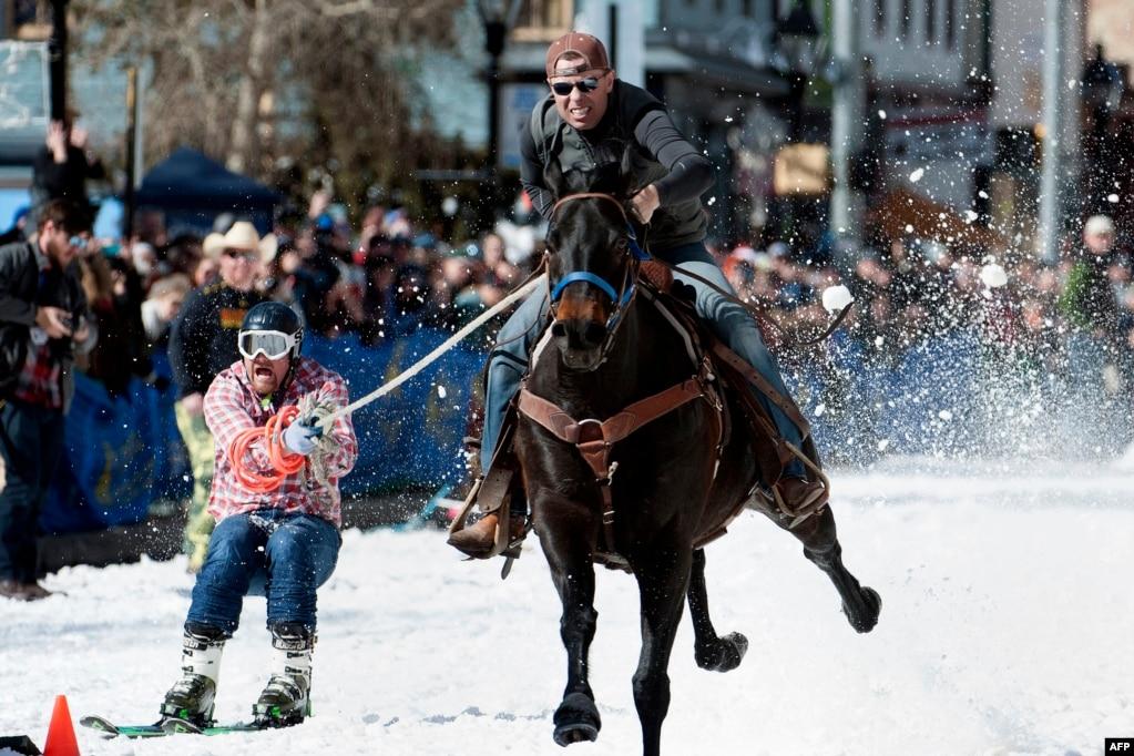 콜로라도주 리드빌의 연례행사인 '제70회 리드빌 스키 조링 주말 경기 대회'에서 에릭 미켈슨 승마선수와 제이슨 달 스키선수가 결승점을 향해 질주하고 있다.