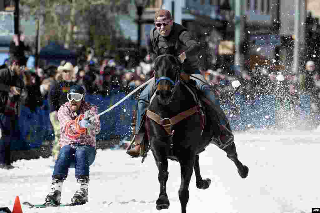 Rider Eric Mikkelson and skier Jason Dahl race to the finish line during the 70th annual Leadville Ski Joring weekend competition in Leadville, Colorado, March 3, 2018.