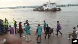 Quelques personnes contemplent, de la plage, un bateau qui passe sur le fleuve Congo, qui sépare Brazzaville et Kinshasa, à Kinshasa, RDC, 29 avril 2014.