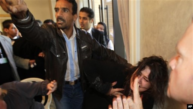 A Ministry of Information official, left, yells at the press to stop filming as he  grabs Iman Al-Obeidi, who said she spent two days in detention after being arrested at a checkpoint in Tripoli, Libya,  and was sexually assaulted by up to 15 men while in