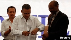 El Salvador's President Mauricio Funes and Daniel Yohannes (R), executive director of MCC, at a school MCC helped fund.