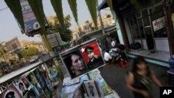 2月23日,緬甸仰光一個路邊售報亭在出售緬甸民主運動領導人昂山素姬和她父親的招貼肖像