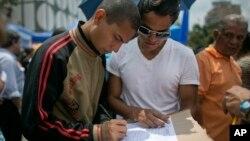 Một người đàn ông ký vào thỉnh nguyện thư yêu cầu truất nhiệm tổng thống Venezuela Nicolas Maduro ở Caracas, ngày 27 tháng 4 năm 2016.