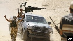 A rebel fighter sitting in a captured Gadhafi forces truck with a mounted weapon is received by comrades occupying high ground overlooking the town of Bir Ghanam, 100 km (62 miles) south of Tripoli, June 30, 2011.