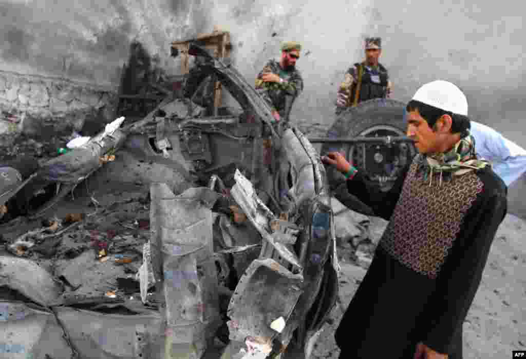 An Afghan man examines the remains of a car after three suicide bombers were killed before they reached Jalalabad airport, which security forces say was their target, in Jalalabad, April 15, 2012. (AP)