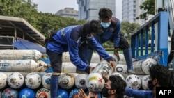 Pekerja menurunkan tangki oksigen di stasiun oksigen darurat di dekat Monas, Jakarta, 5 Juli 2021. (Foto : Mariana/AFP)