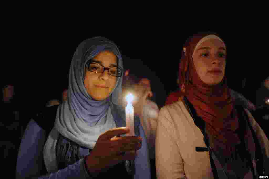 Students Nada Hassanein (left) and Hiba Shaban, members of the Orlando chapter of the Syrian American Council, attend a vigil honoring U.S. journalist Steven Sotloff at the Reflection Pool on the campus of the University of Central Florida, in Orlando, Florida, Sept. 3, 2014.