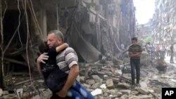 Picha inamuonyesha mwanamme akiwa amembeba mtoto baada ya shambulizi la anga huko Aleppo, Syria, Alhamisi April 28.