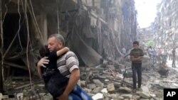 Một hình ảnh được trích ra từ đoạn phim đăng tải trên mạng cho thấy người đàn ông bế một em bé sau trận không kích vào Aleppo, Syria, ngày 28 tháng 4 năm 2016.