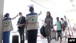 Para petugas memeriksa suhu para pelawat di pos imigrasi Myawaddy, dekat perbatasan Thailand, 23 Maret 2020. (Foto: Reuters)