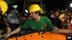 The body of one of two miners recovered on 21 Oct 2010 is loaded onto a truck