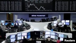 FILE - Traders work at their desks in front of the German share price index, DAX board, at the stock exchange in Frankfurt, Germany, Feb. 19, 2016.