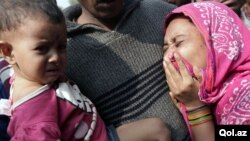 Relatives mourn the death of a garment worker after a fire consumed a garment factory in Savar, Bangladesh, November 25, 2012.