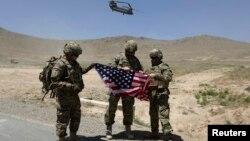 Tentara NATO berpose sambil memegang bendera Amerika sementara helikopter Chinook lepas landar seusai serah terima pengalihan tanggung jawab keamanan di akademi militer di luar Kabul (18/6). Afghanistan menangguhkan perundingan bilateral dengan AS, menyusul rencana dialog AS-Taliban.