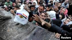 Para pengungsi Suriah yang meninggalkan Aleppo timur, menunggu pembagian makanan dari pasukan Rusia di distrik Jibreen, Aleppo hari Rabu (30/11).
