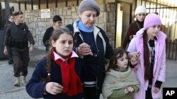 Warga Rusia berjalan bersama setelah melintasi perbatasan Suriah menuju Libanon, Selasa (22/1). Dilaporkan 77 warga Rusia telah meninggalkan negara yang bermasalah itu dan diterbangkan ke Moskow.