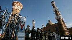 Cảnh sát bán quân sự Trung Quốc trong trang phục chống bạo động canh gác tại lối vào đền thờ Hồi giáo ở trung tâm thành phố Urumqi, Tân Cương.