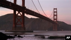 Surfers catch waves late in the day under the Golden Gate Bridge in San Francisco, Wednesday, Jan. 19, 2011. (AP Photo/Eric Risberg)
