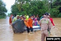 Foto Badan Nasional Penanggulangan Bencana Indonesia (BNPB) ini menunjukkan para penyelamat mengevakuasi penduduk desa dengan perahu karet di daerah banjir di kabupaten Tanah Laut, Kalimantan Selatan, 15 Januari 2021. (Foto: BNPB via AFP)