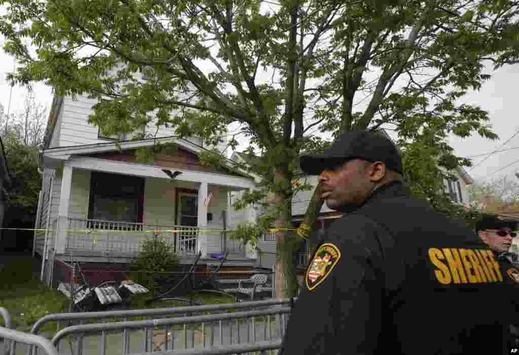 A sheriff deputy stands outside a house where three women escaped after going missing a decade ago, Cleveland, Ohio, May 7, 2013.