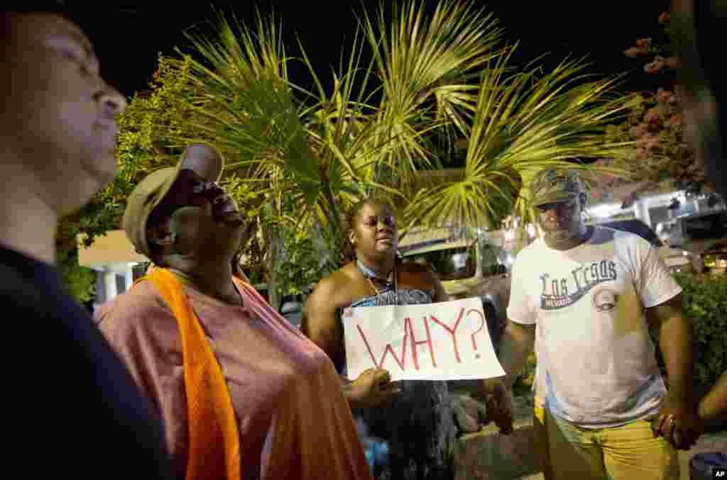 Surreace Cox, of North Charleston, S.C., holds a sign during a prayer vigil down the street from the Emanuel AME Church early Thursday, June 18, 2015, following a shooting Wednesday night in Charleston, S.C.