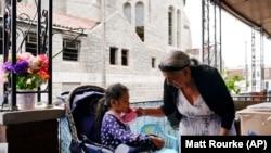 Amanda Brebe, 75, tends to her granddaughter Zuniga Gonzales, 7, in the Kensington section of Philadelphia, Sunday, May 16, 2021