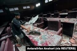 Seorang pria membersihkan ruang sidang yang rusak akibat gempa bumi yang melanda laut 91 km tenggara Blitar, foto di Blitar, Jawa Timur, 10 April 2021. (Foto: Antara/Irfan Anshori via Reuters)