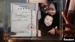 资料照:中国维权律师王全璋的妻子李文足手举全家福照片和天津警方的逮捕通知书。(2018年12月17日)