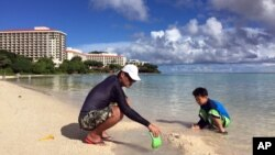 Kenji Kikuchi plays with his son Hideki in Ypao Beach, Tumon, Guam, Aug. 14 2017.