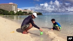 Kenji Kikuchi plays with his son Hideki in Ypao Beach, Tumon, Guam, Aug. 14 2017. Kikuchi was aware of the threat from reading the local newspaper and was a little worried.