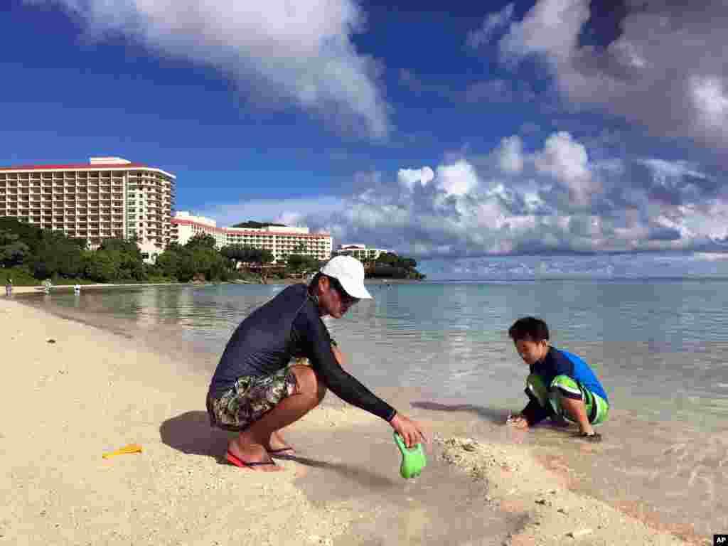 关岛海滨风光如画,碧水金沙。居民仁川健司与他的儿子秀树在关岛的海滩玩耍(2017年8月14日)。仁川健司知道朝鲜的威胁,但不怎么担心。他说,朝鲜的导弹会落在水里,而不是关岛。