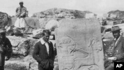 In this 1913 photo, a young T.E. Lawrence (of Arabia), left, is pictured in front of the Long Wall of Sculpture in ancient Turkey. (Photo courtesy of the Joint Turco-Italian Archaeological Expedition)