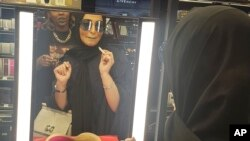 In this Thursday, April 19, 2018 photo, Bahraini singer Jihan Sheib tries on a shade of blue lipstick from Rihanna's new Fenty line that debuted across the kingdom in Sephora stores in Riyadh, Saudi Arabia. Here, where most women cover their faces and hai