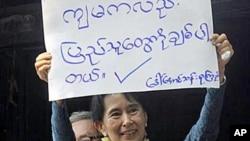 """昂山素季向支持者展示标语""""我也爱人民"""""""