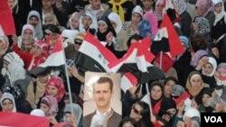 Partidarios del presidente sirio Bashar Al-Assad, esperan por el discurso del gobernante.