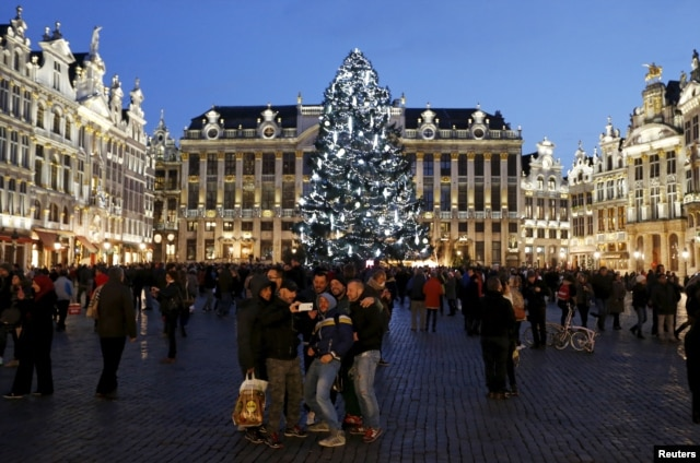 Tourists take a selfie in front of a Christmas tree on Brussels' Grand Place, Dec. 31, 2015, after Belgian police held three people for questioning, as part of an investigation into an alleged plot to carry out an attack in the capital on New Year's Eve.