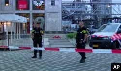 In this image taken from video, officers stand behind a cordoned-off area in Rotterdam, Aug. 23, 2017, after a concert by an American band was canceled following a possible terror threat.